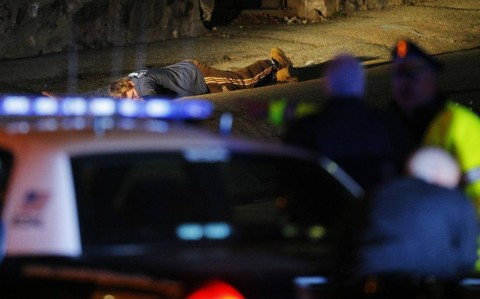 Police officers keep a man on the ground in Watertown